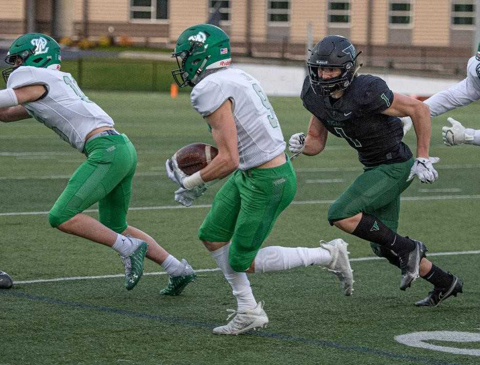 West Linn's Clay Masters, who had two touchdown catches, runs from Tigard's Spencer Kuffel (1). (Photo by Ralph Greene)