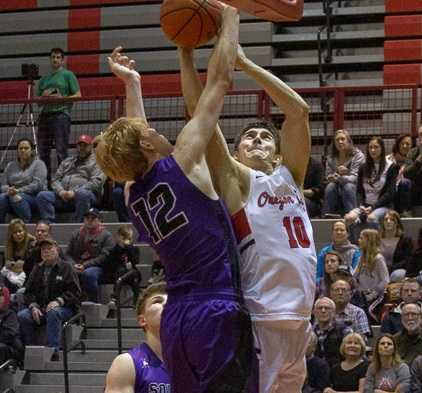 Oregon City's Corban Remsburg (10) is challenged at the rim by South Eugene's Aidan Clark. (Photo by Tamara Peyton)